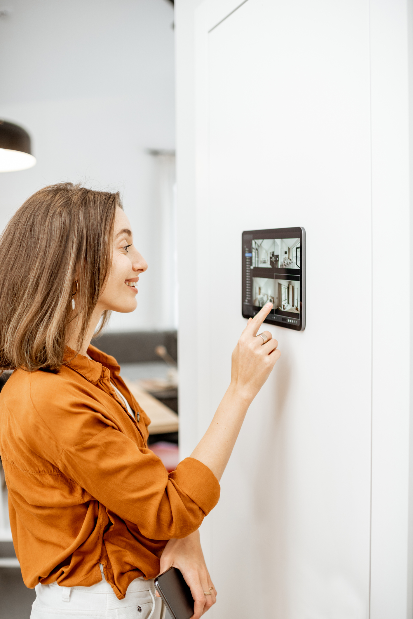 Woman controlling home with video cameras and digital tablet
